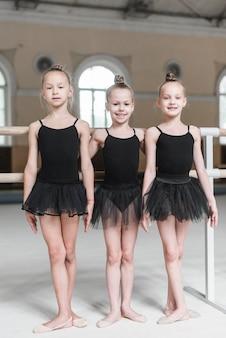 Portrait of three ballerina girls standing in dance studio