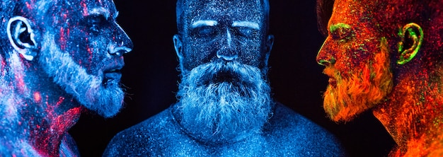 Portrait of three bearded men painted in florescent powders.
