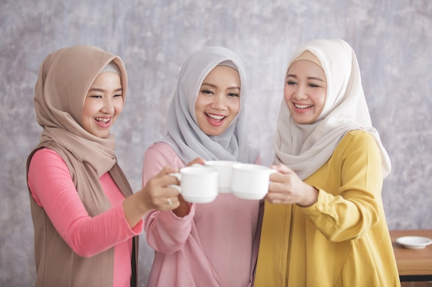 Portrait of three beautiful muslim woman cheers on their coffee after achieve a great work and success