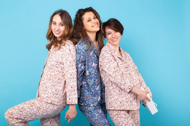 Portrait of three beautiful young girls wearing colorful pyjamas having fun during sleepover isolated over blue wall