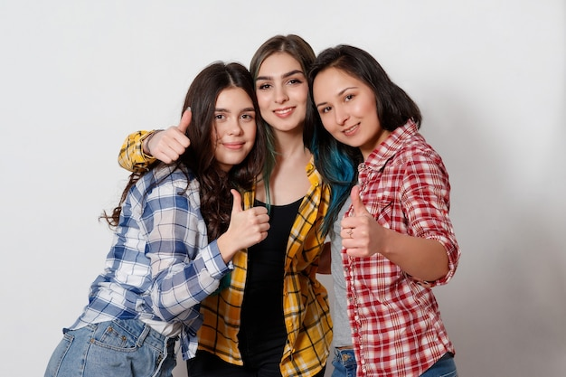 Portrait of three beautiful young happy females smiling joyfully showing thumbs up on gray