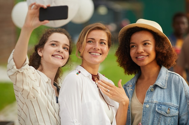 Portrait of three beautiful young women taking selfie photo via smartphone during outdoor party in summer