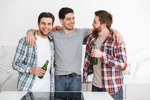 Portrait of a three cheerful male friends celebrating while standing with beer bottles indoors