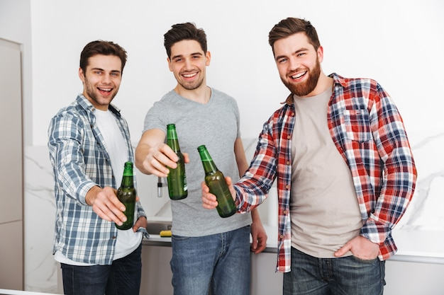 Portrait of a three cheerful male friends toasting with beer bottles shile standing indoors