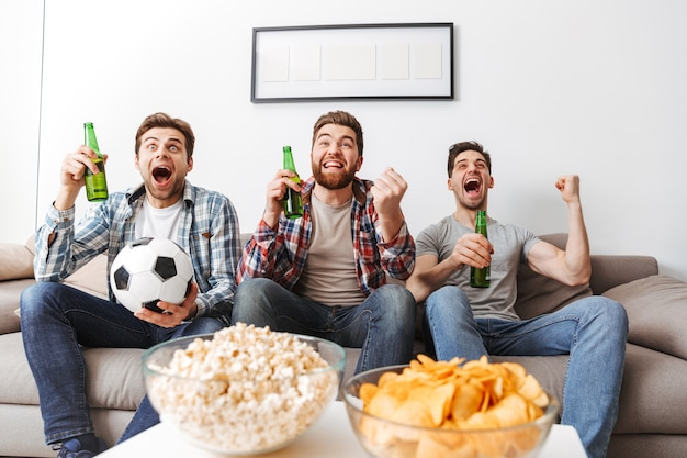 Portrait of three cheerful young men watching football while sitting at home, drinking beer and eating snacks