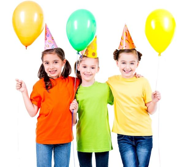 Ritratto di tre bambine sveglie con palloncini colorati e cappello da festa - isolato su un bianco.