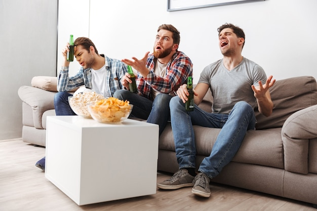Portrait of three disappointed young men watching football while sitting at home with beer and snacks indoors