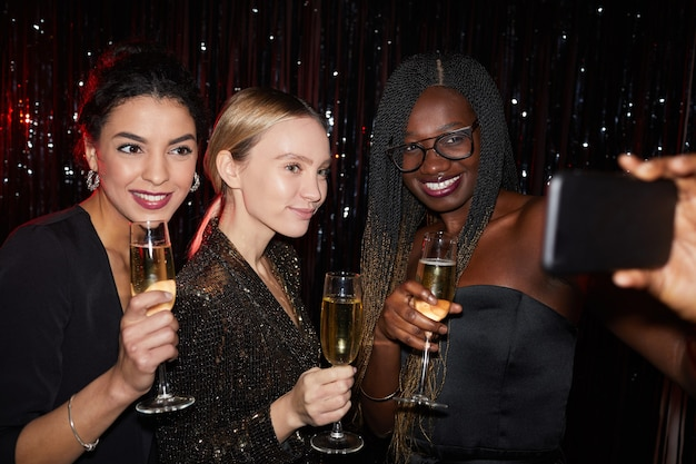 Portrait of three elegant young women holding champagne glasses and smiling while taking selfie photo at party, shot with flash