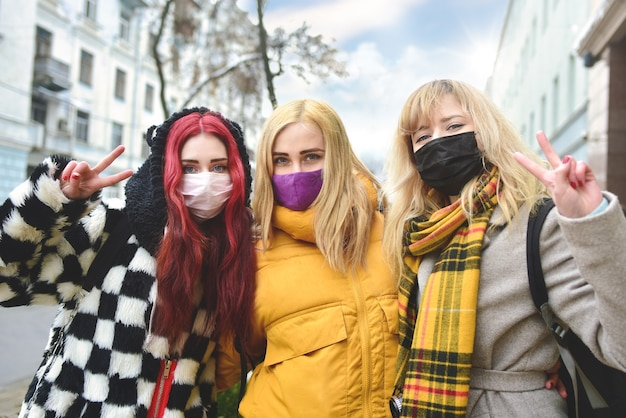 Portrait of three girls with protected wearing masks, making the two finger peace sign hand gesture