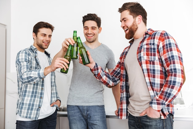 Portrait of a three happy male friends toasting with beer bottles shile standing indoors