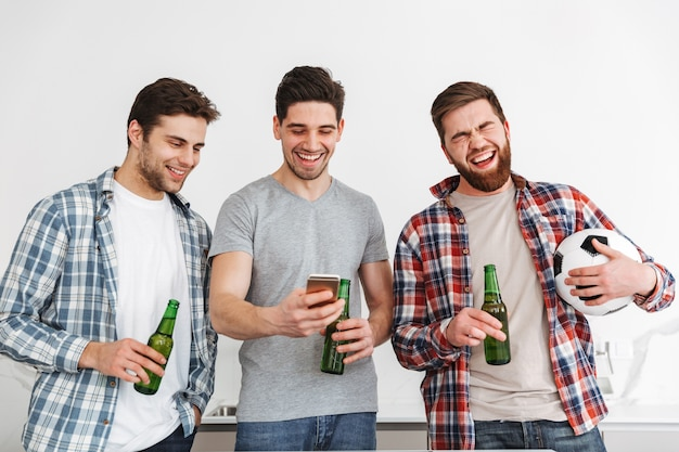 Portrait of three happy young men drinking beer and watching football on mobile phone at home