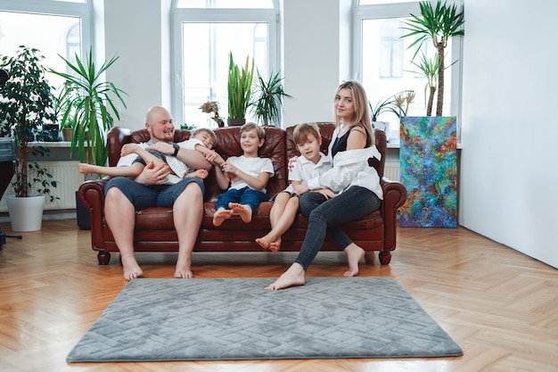 Portrait of three little boys they pose on camera sitting on sofa with their father and mother in modern room.