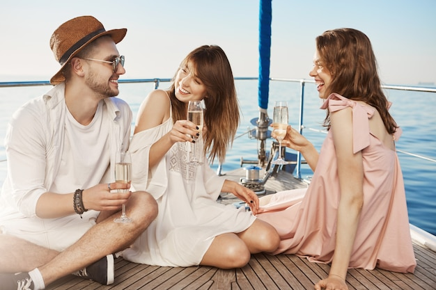 Portrait of three people sitting on floor of yacht while drinking champagne and laughing, enjoying luxurious vacation. two best friends fell in love for same guy and now flirt with him.