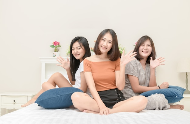 Portrait of three pretty girls smile on bed