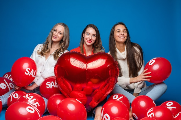 Portrait of three pretty smiling girlfriends in casual clothes sitting with red air balloons with sale and percent sign