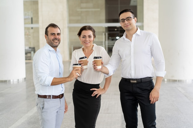 Portrait of three smiling colleagues standing with coffee cups