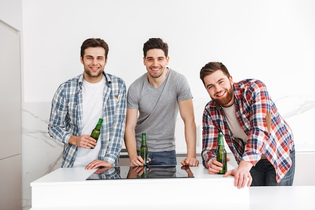 Portrait of a three smiling male friends celebrating while standing with beer bottles indoors