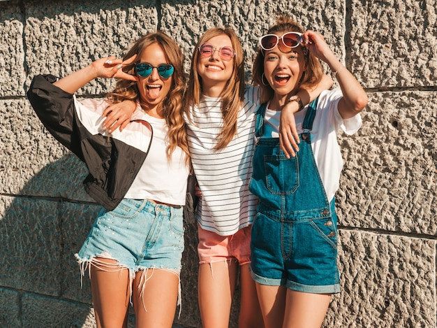 Portrait of three young beautiful smiling hipster girls in trendy summer clothes. sexy carefree women posing near wall in the street.positive models having fun in sunglasses