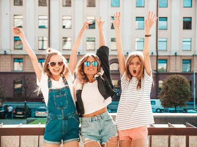 Portrait of three young beautiful smiling hipster girls in trendy summer clothes. sexy carefree women posing on the street.positive models having fun.hugging and raising hands