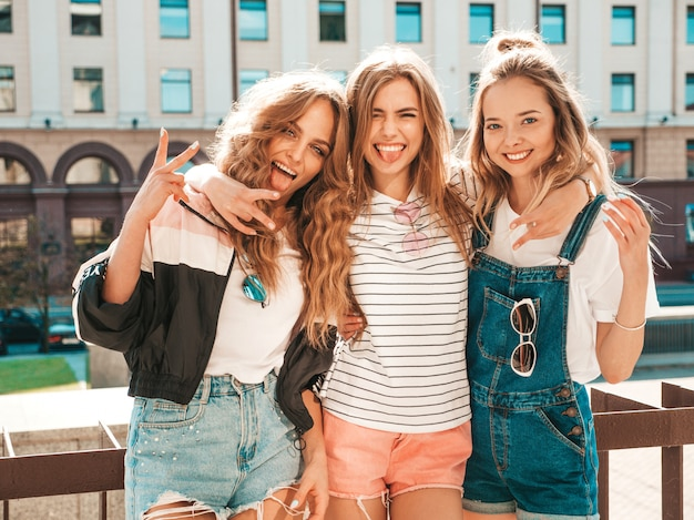 Ritratto di tre giovani belle ragazze sorridenti hipster in abiti estivi alla moda. donne spensierate sexy in posa sulla strada. divertimento di modelli positivi