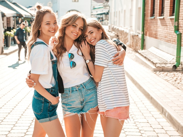 Portrait of three young beautiful smiling hipster girls in trendy summer clothes. sexy carefree women posing on the street.positive models having fun.hugging