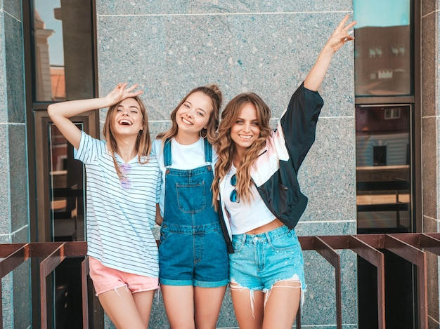 Portrait of three young beautiful smiling hipster girls in trendy summer clothes. sexy carefree women posing on the street.positive models having fun and raise hands