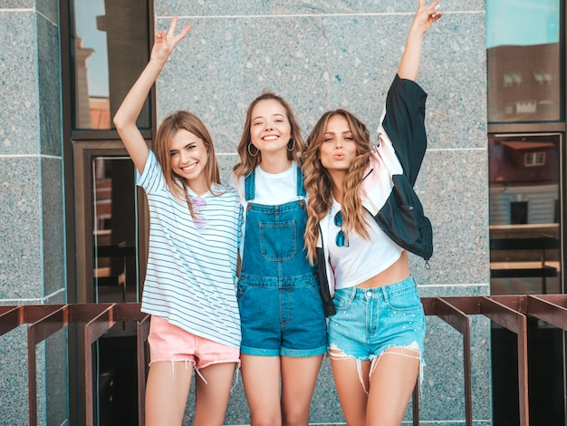 Portrait of three young beautiful smiling hipster girls in trendy summer clothes. sexy carefree women posing on the street.positive models having fun.raising hands