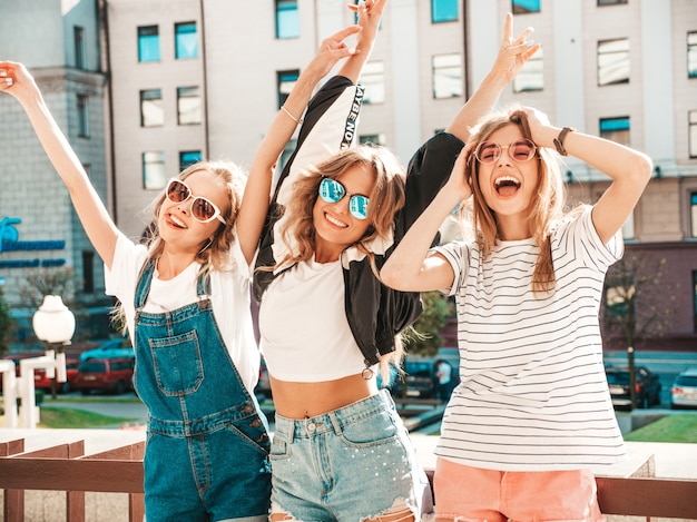 Portrait of three young beautiful smiling hipster girls in trendy summer clothes. sexy carefree women posing on the street.positive models having fun in sunglasses.hugging and raising hands