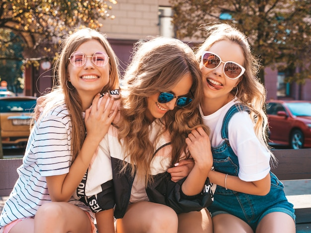 Portrait of three young beautiful smiling hipster girls in trendy summer clothes. sexy carefree women posing on the street.positive models having fun in sunglasses.hugging