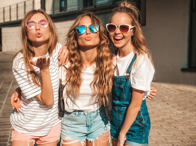 Portrait of three young beautiful smiling hipster girls in trendy summer clothes. sexy carefree women posing on the street.positive models having fun in sunglasses.making duck face