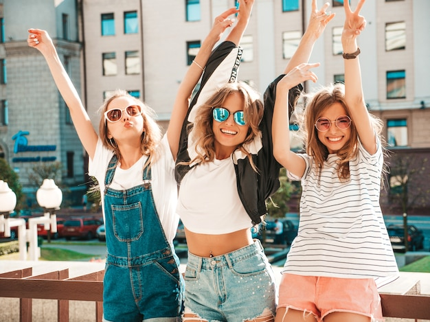 Portrait of three young beautiful smiling hipster girls in trendy summer clothes. sexy carefree women posing on the street.positive models having fun in sunglasses.raising hands