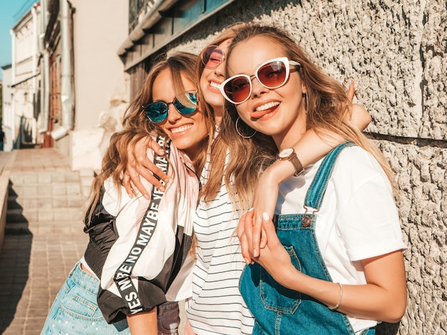 Portrait of three young beautiful smiling hipster girls in trendy summer clothes. sexy carefree women posing on the street.positive models having fun in sunglasses.shows tongue