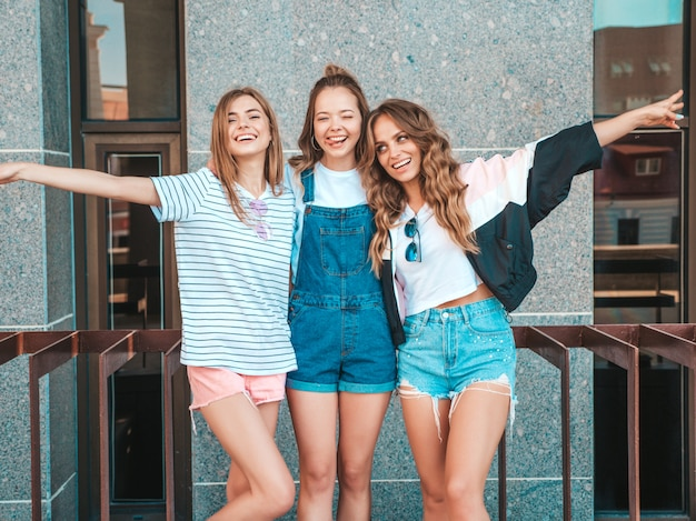 Portrait of three young beautiful smiling hipster girls in trendy summer clothes. sexy carefree women posing on the street.positive models having fun.they raise hands