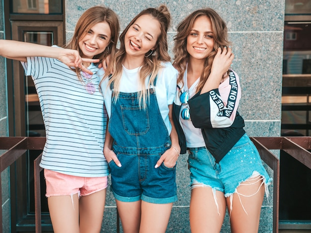 Portrait of three young beautiful smiling hipster girls in trendy summer clothes. sexy carefree women posing on the street.positive models having fun.they show tongue and peace sign