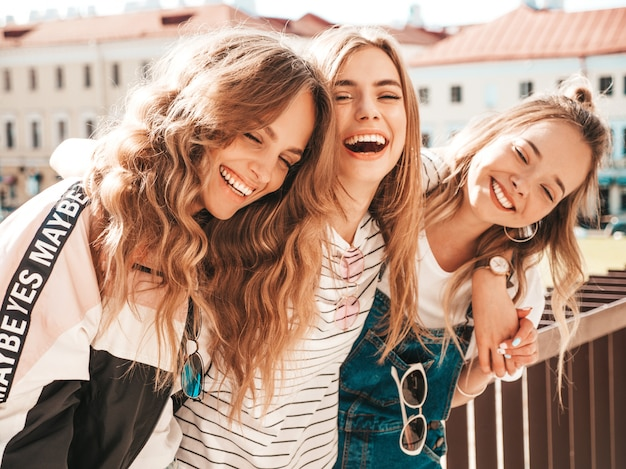 Portrait of three young beautiful smiling hipster girls in trendy summer clothes. sexy carefree women posing on the street.positive models having fun
