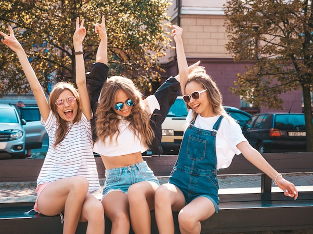Portrait of three young beautiful smiling hipster girls in trendy summer clothes.sexy carefree women sitting on the bench in the street.positive models having fun in sunglasses.raising hands