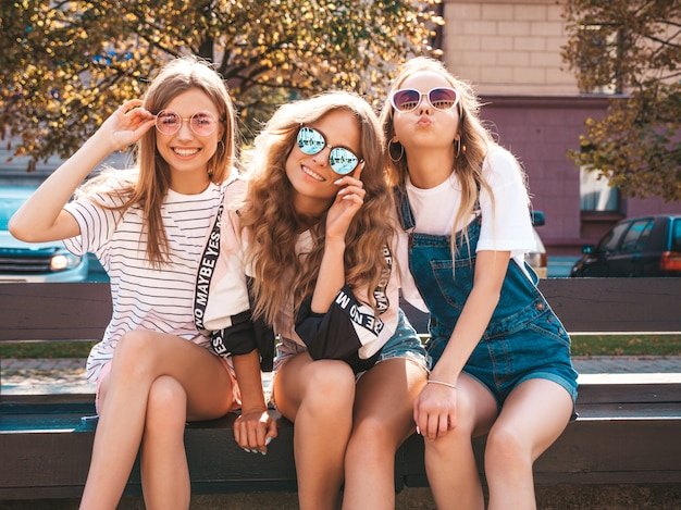 Portrait of three young beautiful smiling hipster girls in trendy summer clothes.sexy carefree women sitting on the bench in the street.positive models having fun in sunglasses