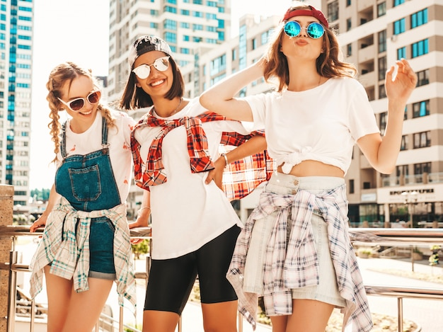 Portrait of three young beautiful smiling hipster girls in trendy summer clothes.