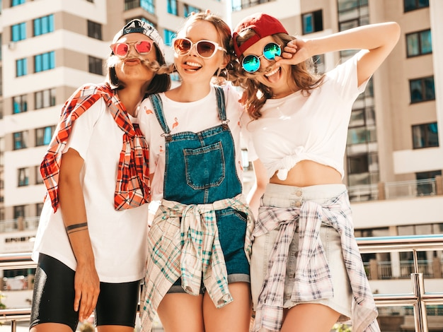 Portrait of three young beautiful smiling hipster girls in trendy summer clothes