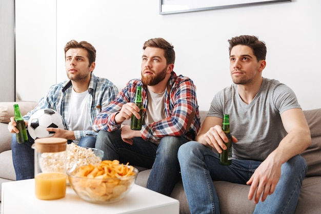 Portrait of three young men watching football while sitting at home , drinking beer and eating snacks