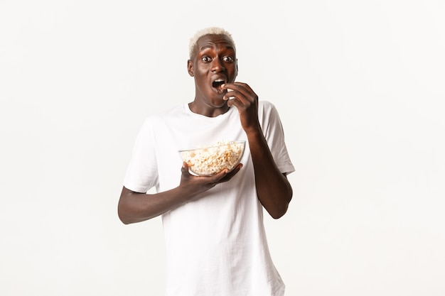 Portrait of thrilled and amazed african-american young man enjoying watching movie or tv series, eating popcorn with excited expression
