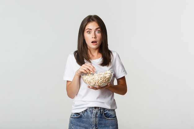 Ritratto di giovane donna entusiasta e stupita che mangia popcorn e guarda film o serie tv.