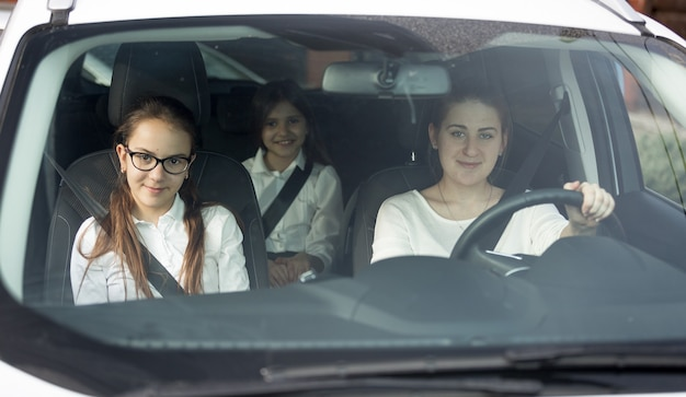 차에 타고 있는 행복한 미소 짓는 어머니와 두 딸의 앞 유리를 통한 초상화