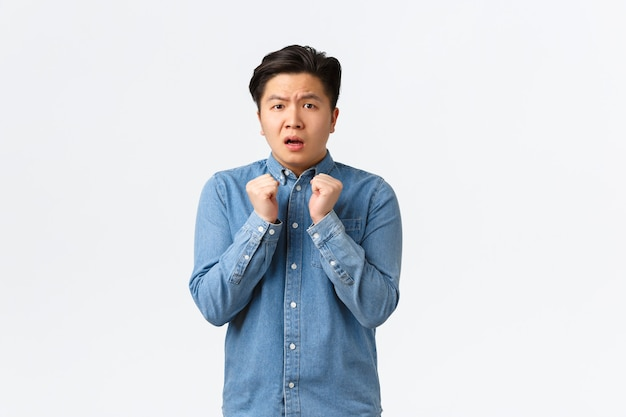 Portrait of timid and insecure young asian man feeling cornered or scared, holding hands tight to chest, shivering fear, looking anxious at camera, standing frightened over white background.