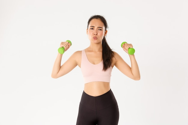 Portrait of tired asian girl in sportswear, looking exhausted during workout, exercise at home with online coach, lifting dumbbells, white background.