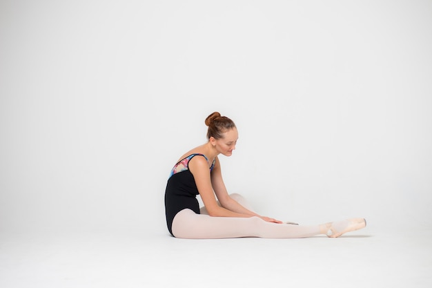 Portrait of a tired ballerina on a white background close-up, a young woman is sitting on the floor.