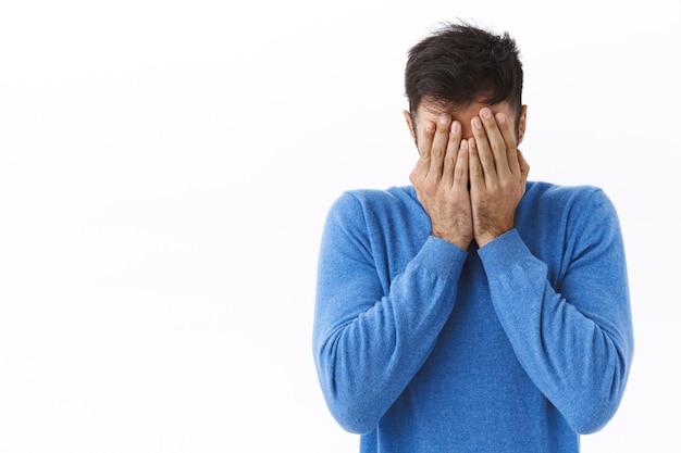 Ritratto di ragazzo caucasico stanco e depresso, nascondendo il viso, facepalm e singhiozzando, sentirsi angosciato ed emotivo burnount lavorando a distanza da casa durante la quarantena pandemica, muro bianco