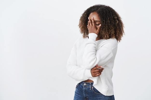 초상화 피곤 지친 아프리카계 미국인 곱슬 머리 여자 facepalming 프레스 손바닥 얼굴 눈을 감고 지친 눈, 귀찮은 짜증 벙어리 픽업 라인, 흰색 벽