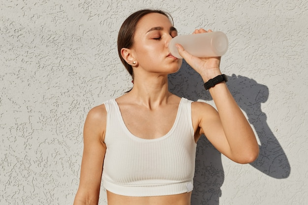 Portrait of tired fitness girl feeling thirsty after sports exercises drinking water from bottle