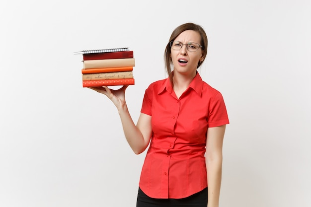 Portrait of tired frustrated upset business teacher woman in red shirt glasses holding stack text books in hands isolated on white background. education or teaching in high school university concept.
